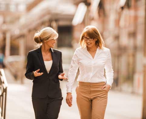 Two business women walking down street talking